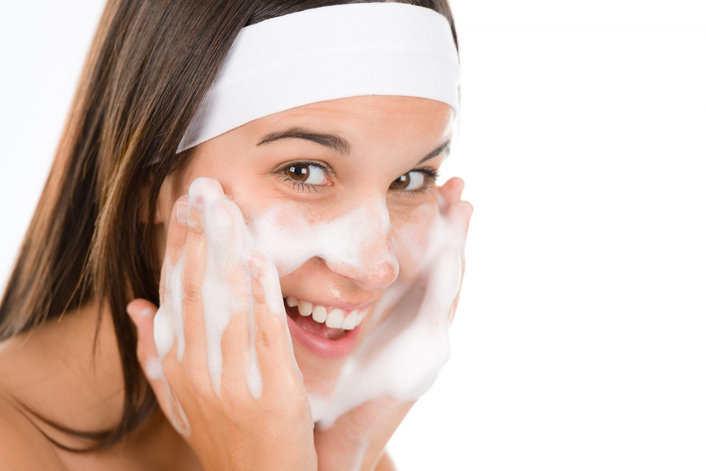 Teenager problem skin care - woman wash face with cleansing foam