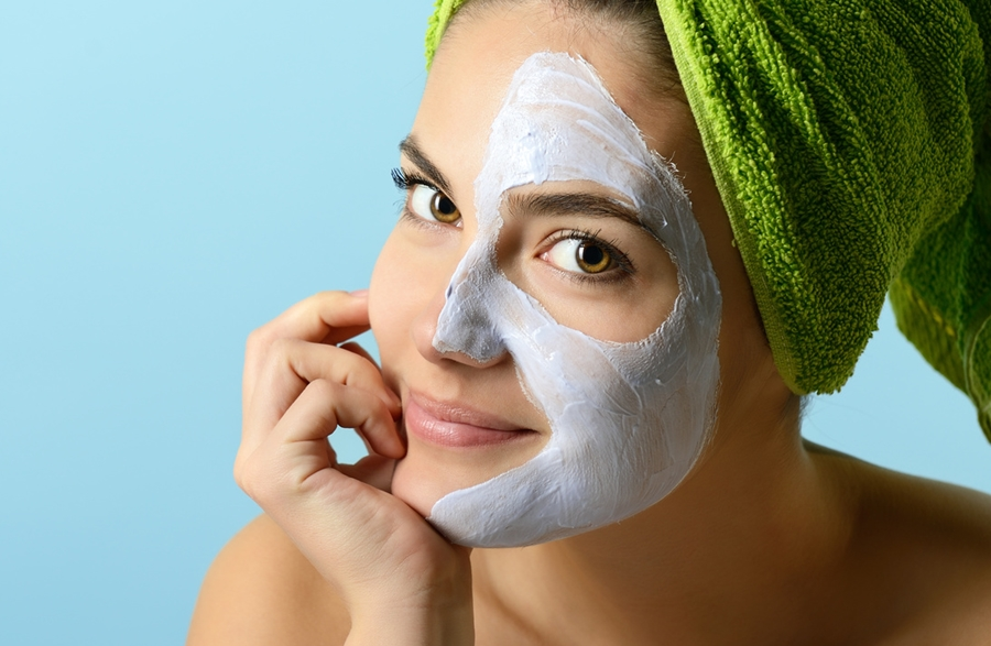 Beautiful young woman with facial mask, beauty treatment over blue